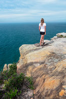 Woman gazing out from the cliff top views Royal National Park