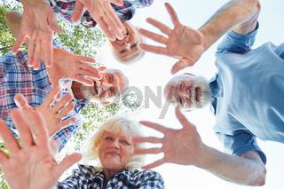 Winkende Hände von Senioren im Sommer