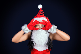 Bearded Mrs. Claus looks to the camera with her hands imitating the telescope.