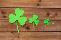 green paper shamrocks on wooden background