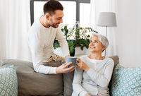 adult son bringing coffee to senior mother at home