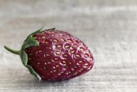 Strawberry berry on the surface of a wooden table.