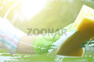 Male hand in green glove with yellow sponge washing car window