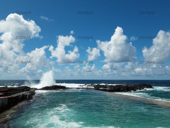 ocean wave splash on rocks at coast on a sunny day with blue sky  -