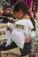 Indian girl in national clothes sells the products of her weaving, as usual on weekdays on the most famous markets in South America, in Otavalo, Ecuador