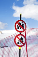 Snowy ski slope, fence and two prohibitory traffic sign on ski resort