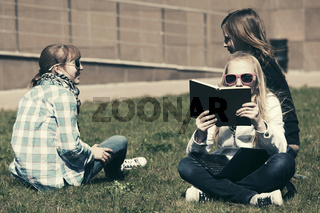 Group of happy school girls sitting on a grass in campus