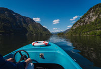 Handsome young guy controls a motorboat on a mountain lake