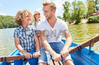 Vater und Sohn rudern gemeinsam im Ruderboot