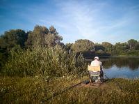 A man fishing on the shore of a beautiful lake.