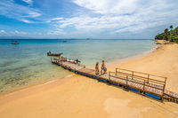 A couple arrive on a golden sand beach of a paradise island along a jetty.