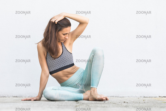 Fit sporty active girl in fashion sportswear sitting on the floor in front of gray wall.