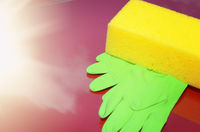 Yellow sponge and green gloves laying on car bonnet. Wash waxing or care concept. Place for text