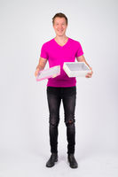 Full body shot of happy young handsome man holding open gift box