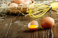 Raw organic brown chicken broken eggs with yolk wicker basket and whisk on kitchen wooden table