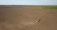 Tractor cultivates the field, spring works on farmlands. Photo from the drone