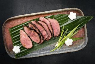 Japanese barbecue wagyu aged fillet steak slices with daikon and leek as top view on a plate
