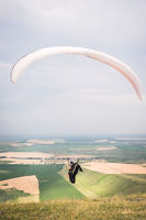 A man paraglider taking off from the edge of the mountain with fields in the background. Paragliding sports