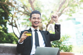 Man holding credit card and cheering.