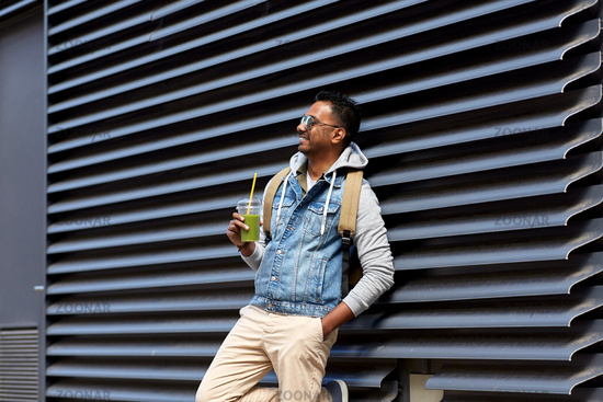 man with backpack drinking smoothie on street
