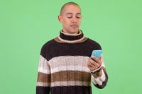 Handsome bald multi ethnic man using phone ready for winter