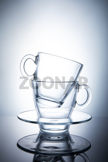 Two isolated transparent tea cups with saucers