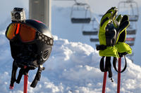 Protective sports equipment on ski poles and chair-lift at background