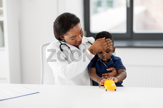 doctor with measuring baby's temperature at clinic