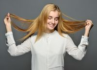 Smiling blonde woman with long hair in white blouse.