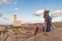 Solitary young female traveler watches a beautiful sunset over lighthouse and spectacular rock formations of Capo Testa, Sardinia, Italy.