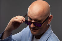 bald man in black glasses on a gray background