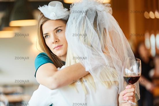 Melancholische Frau umarmt Braut mit Brautschleier