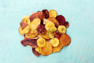 Dry fruit and vegetable chips, healthy vegan snack, a mixed heap on a blue background