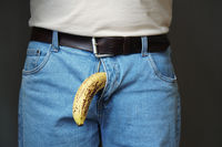 old banana hanging from genital area of unrecognizable man impotence concept