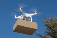 Unmanned Aircraft System (UAV) Quadcopter Drone Delivering Package