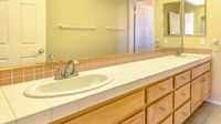 Panorama Double vanity unit with wood cabinets inside the small bathroom of a house
