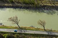 Blick von oben auf ein Auto auf einer Landstrasse an einem Fluss