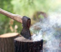 Axe in tree stump and campfire with smoke in summer forest