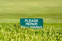 Close up of a golf course sign that reads Please Repair Ball Marks