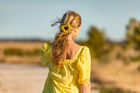 Woman outdoors in sunshine sunflower in her wavy hair
