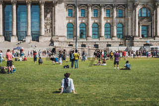 Many people on meadow in public park in front of the Reichstag building  on a sunny, summer day
