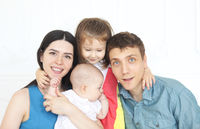 Happy young parents with their adorable little kids at home