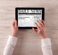 Hand with tablet reading news