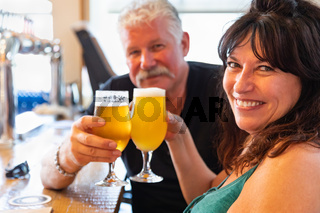 Attractive Middle-Aged Couple Toasting Glasses of Micro Brew Beer At Bar