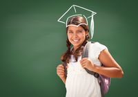 Young Hispanic Student Girl Wearing Backpack Front Of Blackboard with Fireman Helmet Drawn In Chalk Over Head