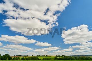 Blauer Himmel mit Wolken vor grüner Wiese