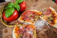 Original Italian Pizza alla diavolo on brown wood background. Pizza with Hot peppers and salami close up