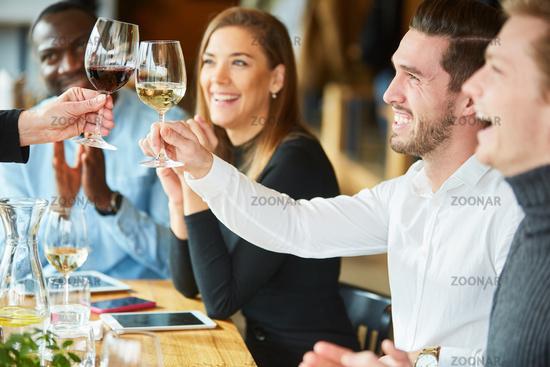 Freunde stoßen an mit Glas Wein im Restaurant