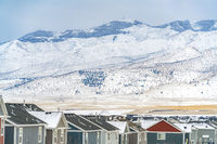 Exterior of homes against sky and mountain blanketed with snow in winter