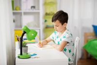 little boy writing to notebook at home